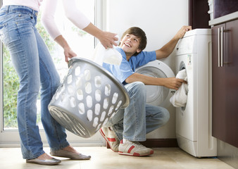 A mother and son loading the washing machine