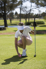Woman playing golf, teeing up