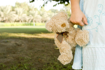 A young girl holding a teddy bear