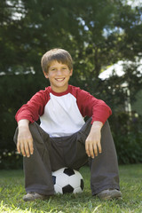 Young boy sitting on a football