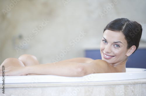 A young woman laying in a bath