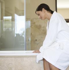A woman sitting on the edge of a bath