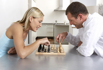 Young couple playing a game of chess in the kitchen
