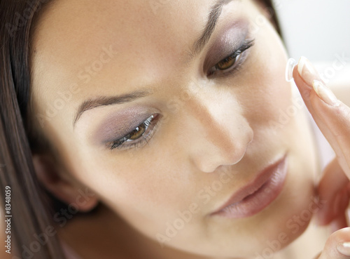 Young woman inserting a contact lens, close-up