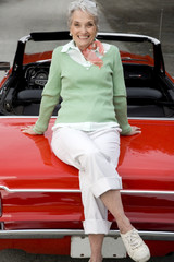 A senior woman sitting on a sports car