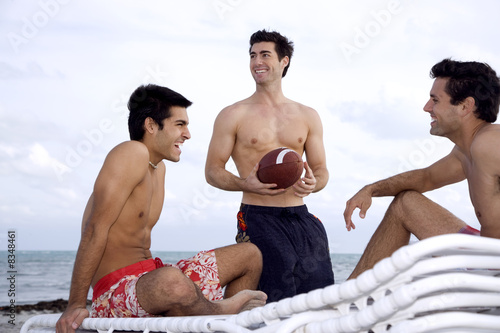 Three young men sitting on a beach