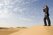 A man standing in the desert looking through binoculars