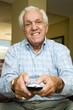 An elderly man using a TV remote control