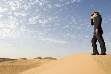 A man standing in the desert looking through binoculars