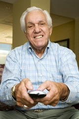 An elderly man using a TV remote control