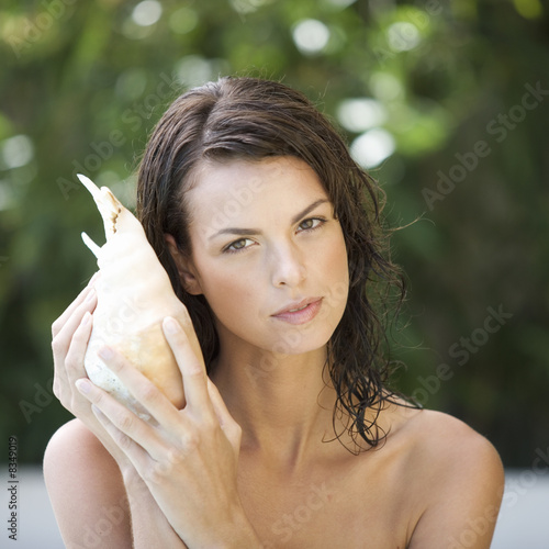 A young woman listening to a sea shell