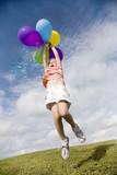 A young girl holding a bunch of balloons