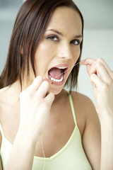 Woman using dental floss, close-up