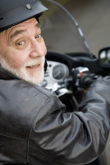 A senior man riding a motorbike