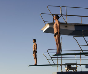 Two divers standing on diving boards