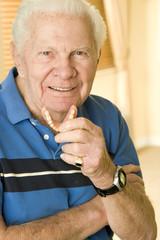 An elderly man holding his false teeth