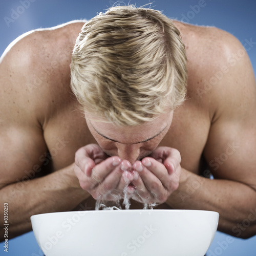 A young man washing his face