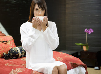 A woman drinking from a bowl sitting on a bed