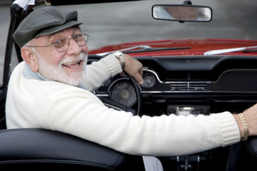 A senior man driving a sports car