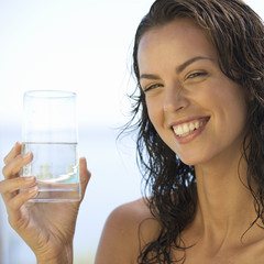 A young woman drinking a glass of water