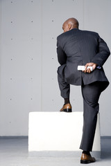 A businessman standing on a block