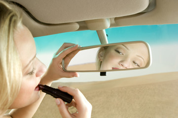 A young woman using a rear view mirror to apply make-up