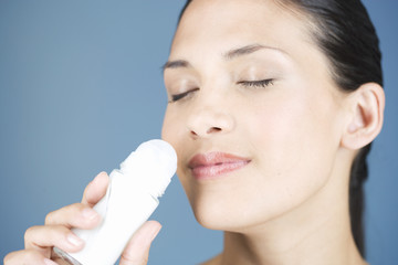 A young woman smelling a de-odorant roll-on