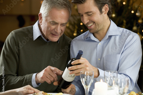 A father and son looking at a wine bottle