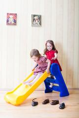 Two adorable girls having fun atop playground slide