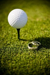 Wedding rings lying on a golf green next to a ball on tee