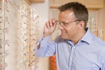 Man trying on eyeglasses at optometrists smiling