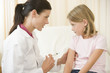 Doctor giving needle to young girl in exam room