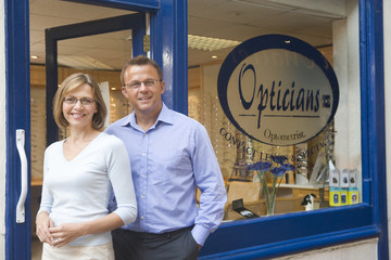 Couple standing at front entrance of optometrists smiling