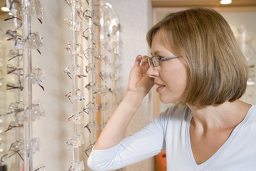 Woman trying on eyeglasses at optometrists