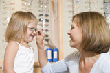 Woman trying eyeglasses on young girl at optometrists smiling