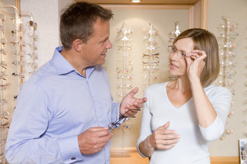 Couple trying on eyeglasses at optometrists