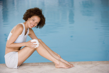 Woman sitting poolside using shower puff on leg smiling
