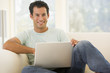 Man in living room using laptop smiling