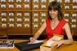 A beautiful young college girl working with a cardfile drawer