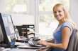 Woman in home office using computer and smiling