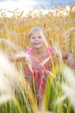 Little girl in a wheat field. Against backdrop of cloudy skies poster