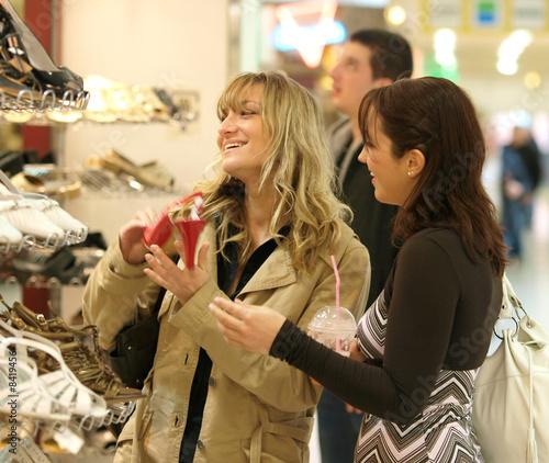 Leinwanddruck Bild Zwei junge Mädchen, Frauen mit grosser Freude beim Schuhe Einkau