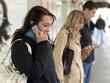 Junge Leute /Jugendliche telefonieren, schicken SMS mit dem Hand