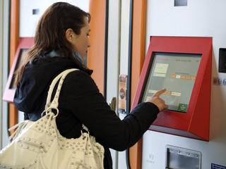 Eine junge Frau an einem Fahrscheinautomaten.