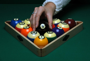 A woman places Balls on a pool (billard) table before play