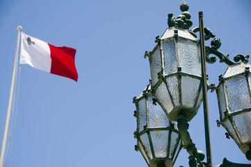 flag malta with historic street lamp valletta