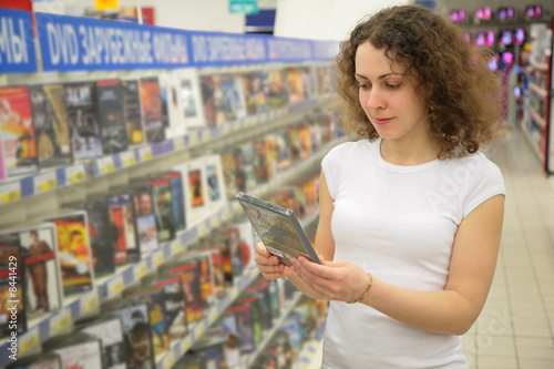 young woman in shop holds in hands dvd