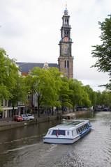 canal scene with tourist boat westekerk amsterdam
