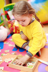 Cute child playing with puzzle