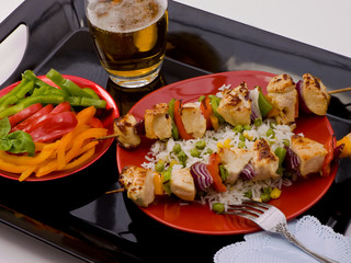 Chicken on black tray with a skewer with rice, peppers and beer.